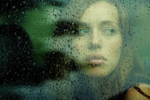 빗방울 떨어진 창문 너머를 보는 여인
