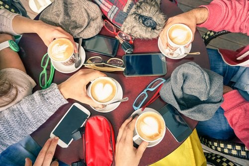 핸드폰을 두고 커피 마시는 친구들
