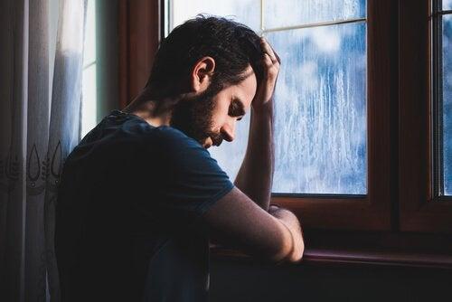 창가에 서서 고개를 숙인 남자 사진