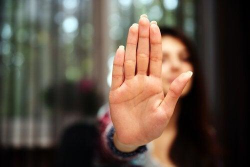 여자가 거절의 뜻으로 손바닥을 앞으로 내밀고 있는 사진