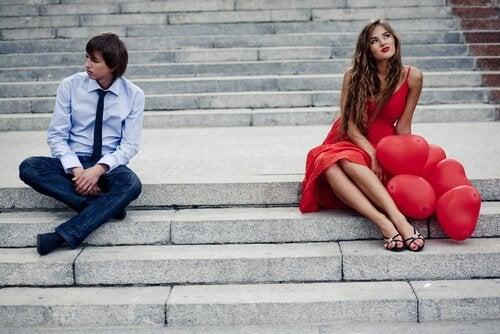 계단 위에 앉아 서로 다른 곳을 보는 커플 사진