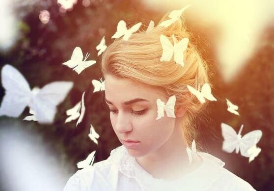 얼굴 주변을 나비가 날아다니는 여자 사진