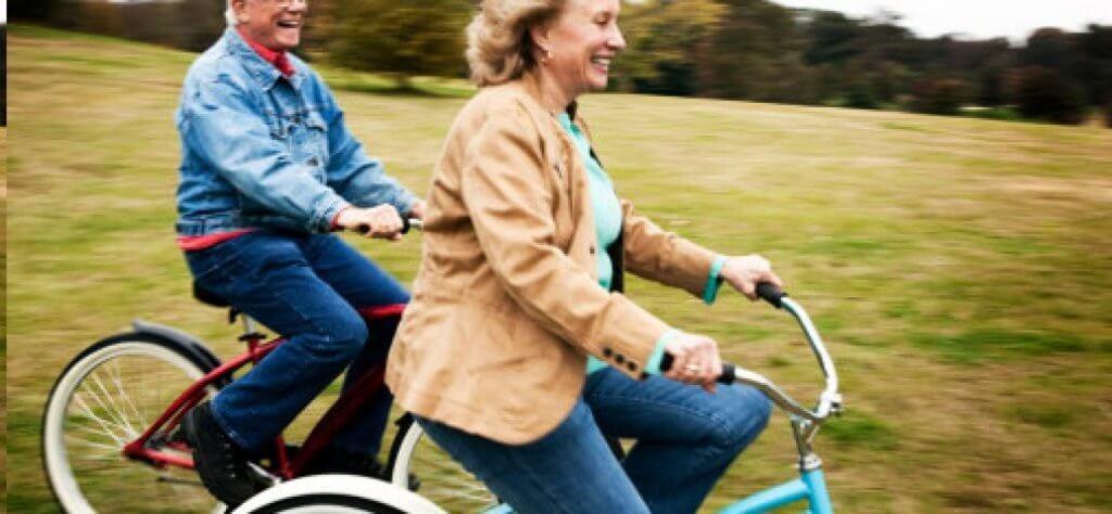 자전거를 타며 웃고 있는 두 나이든 커플 사진