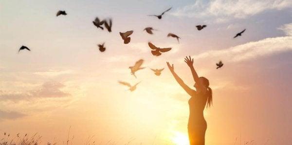 새떼를 향해 두 팔을 벌린 여자 사진