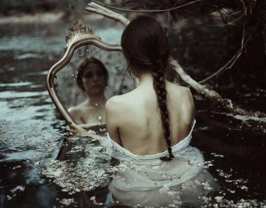 물 속에서 거울을 보고 있는 여자 사진