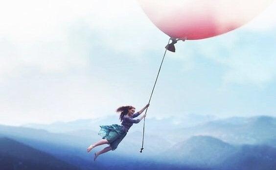 엄청 큰 핑크 풍선에 매달려 날아가는 여자 사진