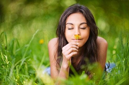 풀밭에서 꽃향기를 맡는 여자 사진