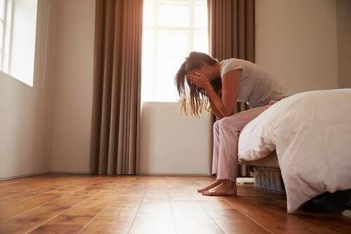 침대에 걸터앉아 울고 있는 듯한 여자 사진: 질 경련