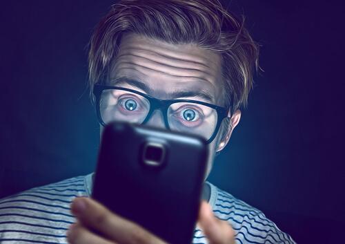 밤에 스마트폰을 보는 남자