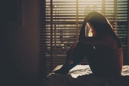 편집증 - 머리에 손을 대고 앉아 괴로워 하는 여성