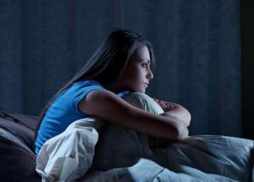 불면증 약리 치료: 정의 및 유형 - 침대에 웅크리고 있는 여자